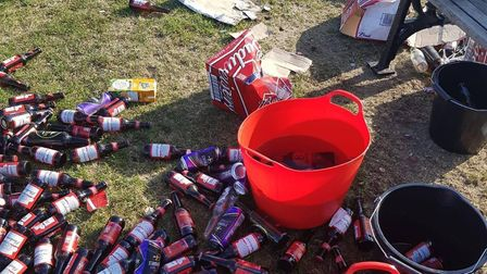 Buckets of beer, cardboard boxes and bottles were left behind, littering an area near a park bench.
