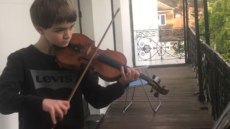 Thomas Ormond, 11, playing the violin on his balcony. He says he'll continue raising money for the N