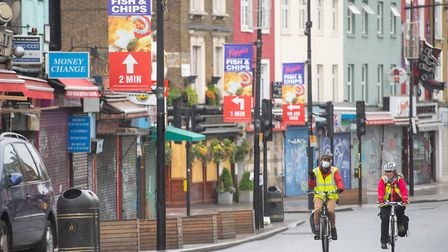Cyclists ride past shuttered shops on Camden High Street. Picture: Dominic Lipinski/PA Images