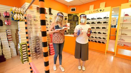 Zdenka Ivankova (left) and owner Jenny Ho at Cubs shoe shop donned in PPE. Picture: Polly Hancock