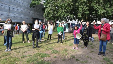 Organisers, speakers and attendees on the green in front of Hornsey Town Hall raise a fist in suppor