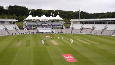 West Indies and England players observe a minute's silence ahead of the start of play on day one of