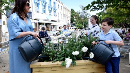 Chief planting officer Jane Lyons and her children Ellie, 13 and Max, 9, give the planters a water.