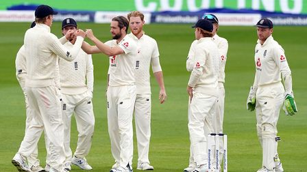 England's Chris Woakes (centre) celebrates with his team-mates after taking the wicket of West Indie