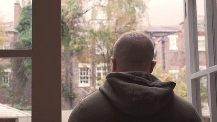 A man looking outside from James' Place in Liverpool