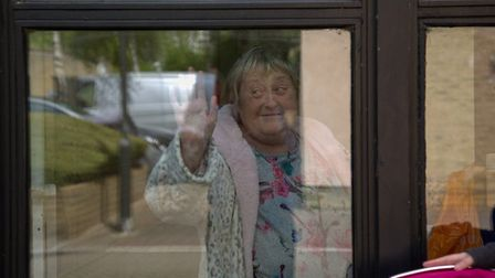 Dawn gives photographer Ruth a thumns up from her locked-down window. Picture: Ruth Corney