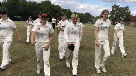 Millie Pope, centre holding cap, leads the North London women off the field after her efforts with b