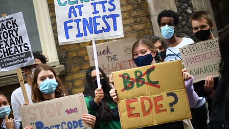 People take part in a protest outside the Department of Education in Westminster, London, over the g