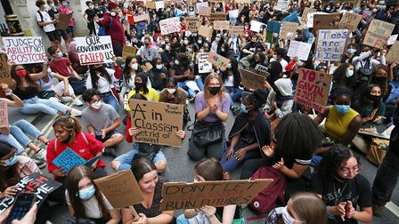 People take part in a protest outside the Department for Education, London, in response to the downg