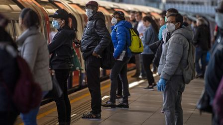 Passengers wearing face masks on a platform at Canning Town underground station in London. Picture: