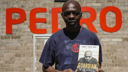 James Cook MBE stands outside Pedro Club with his autobiography aptly titled Guardian Of The Streets