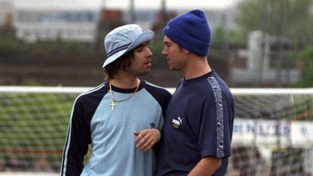 Liam Gallagher and Damon Albarn on the pitch at Mile End Stadium in 1996. Picture: David Cheskin/PA