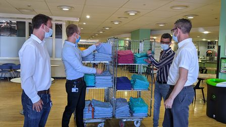 Harry (left) with volunteers Richard Sugar and Rui Mendes hand out scrubs. Picture: Royal Free Hospi