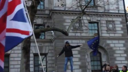 A Tommy Robinson supporter attempts to set alight to an EU flag. (Image: Jonathan Spinks/Twitter)