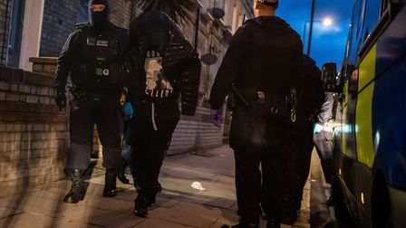 Metropolitan Police officers arrest an occupant of a property during a raid on York Way. Picture: A