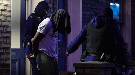 Metropolitan Police officers arrest an occupant of a property during a raid on York Way in London,