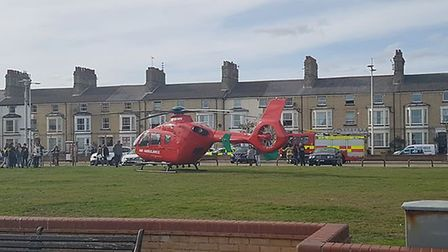 A woman has been taken by air ambulance to hospital after falling out of a window in Marine Parade,
