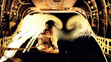 An aircrewman from 18 sqn RAF watches decoy flares through the rear door of a Chinook Helicopter. Pi