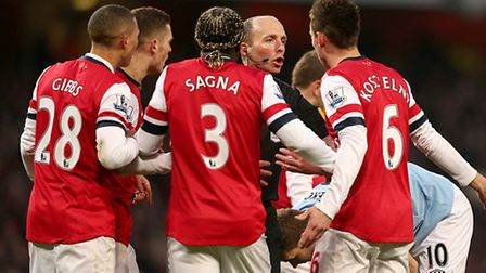 Arsenal players appeal to the referee Mike Dean (centre) after he sent off Laurent Koscielny for fou