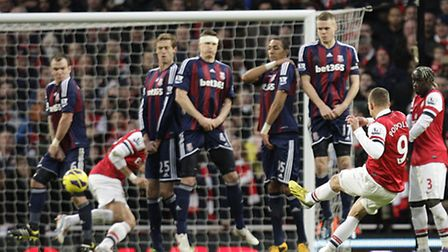 Arsenal's Lukas Podolski scores the winning goal from a free-kick against Stoke City. Photo: Sean D