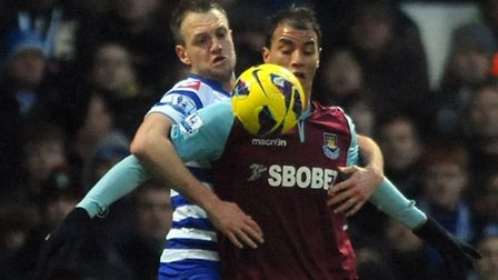 West Ham's Marouane Chamakh appears to be held back by QPR's Clint Hill.