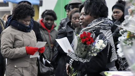 Joseph Burke-Monnerville's mother Linda holds flowers at a vigil in Hackney on Saturday, a week afte