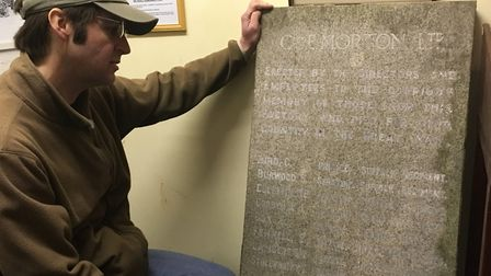 Robert Jarvis, curator at the Lowestoft War Memorial Museum, with a headstone of the workers that us