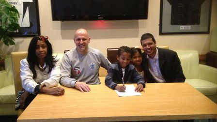 Eight-year-old Deven Solanki signing the contract for QPR