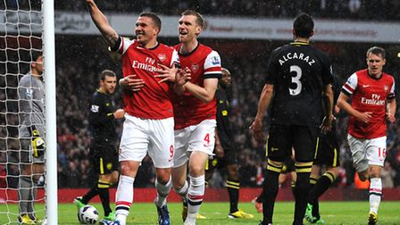 Arsenal's Lukas Podolski (left) celebrates with Per Mertesacker after opening the scoring in the vic