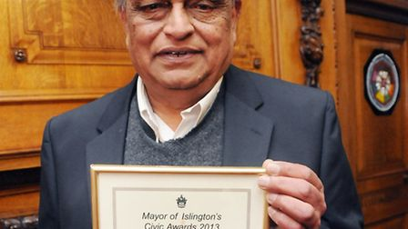 Ashok Patel receiving his Islington community hero award. Pic by Dieter Perry