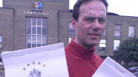 Cllr Paul Lorber holds up books of the visitor parking scratchcards