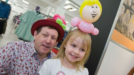 Entertainer Roger Daws makes balloon animals and faces for children attending Marks & Spencer Hollow