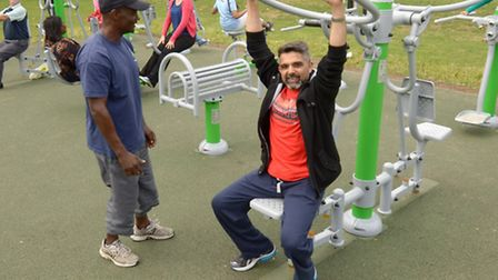 Cllr Muhammed Butt trying out one of the outdoor gyms with coaching from Brent Council instructor B