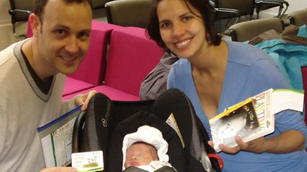 Agustin Arias, 9 days old, celebrates her library card with father and mother Leandro and Laura