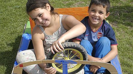 Lilia, 8, and her brother Lyes, 6, showing off the car they built