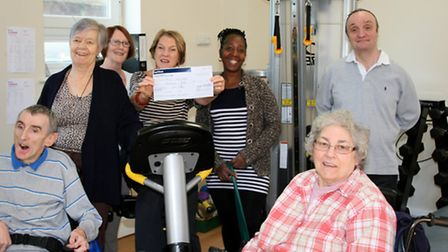 Marianne Gray holding a cheque with members of the Outlook gym