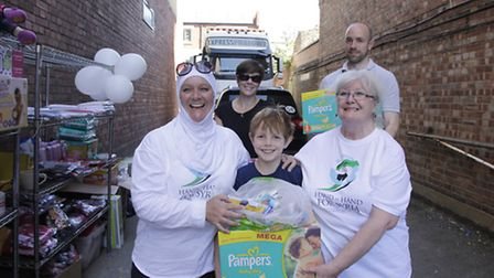 Joseph Purcell (8) with parents Beth and Greg handing in donations to Iman Mujahed (left) and Vivien