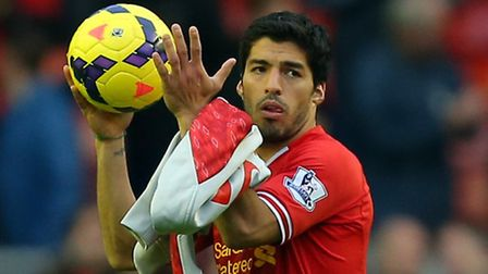 Liverpool's Luis Suarez leaves the pitch with the match ball after scoring three goals against West