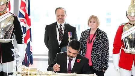 Cllr Muhammed Butt signs a pledge of support for the military called the Armed Forces Covenant.