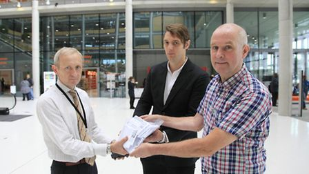 Peter Goss accepted the petition from Joel Davidson and John Warren. Picture credit: Jan Nevill