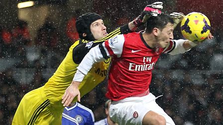 Chelsea goalkeeper Petr Cech punches the ball off the head of Arsenal's Mesut Ozil