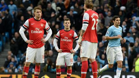 Arsenal's Jack Wilshire shows his dejection after Manchester City 5th goal with Aaron Ramsey (left)