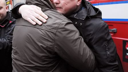 Tearful firefighter Alex Badcock is consoled by a colleague