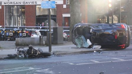 Nissan and charred bike strewn on the road after crash - Xavier Keane