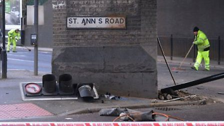 Workers clear the scene where two men died following a police chase in the early hours of Good Frida
