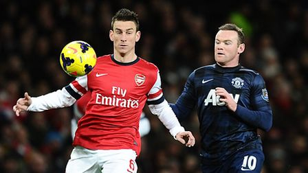 Arsenal's Laurent Koscielny and Manchester United's Wayne Rooney battle for the ball