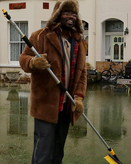 Kye Gbangbola clearing flood waters from outside his home near Chertsey Bridge in Chertsey, Surrey