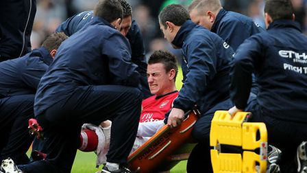 Arsenal's Laurent Koscielny is treated on the pitch after picking up an injury