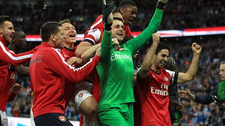 Arsenal's goalkeeper Lukasz Fabianski is mobbed by his team-mates after his penalty saves. Picture: