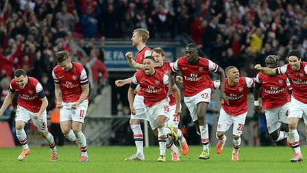 Arsenal players react after Santi Cazorla's winning penalty against Wigan. Picture: PA